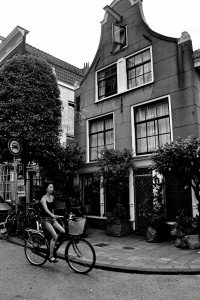 A woman biking through a side street in Amsterdam, Netherlands.