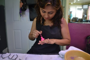 Castillo test a bright pink nail polish on her own nails in order to present her costumer with the exact shade.