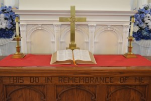 A Bible, a cross, candles and flowers line the altar at St John Baptist Church on September 11, 2016. The wording engraved at the bottom of the altar is a reference to 'The Last Supper.'