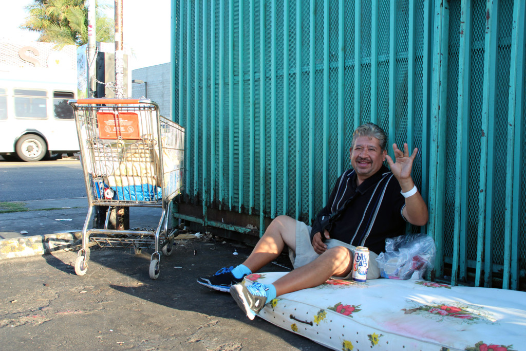 Edgar sits on a bed in the parking lot of Numero Uno Market with a can of Colt 45 by his side.